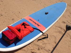 SUP Board, Paddle, Life jacket and water on sandy beach