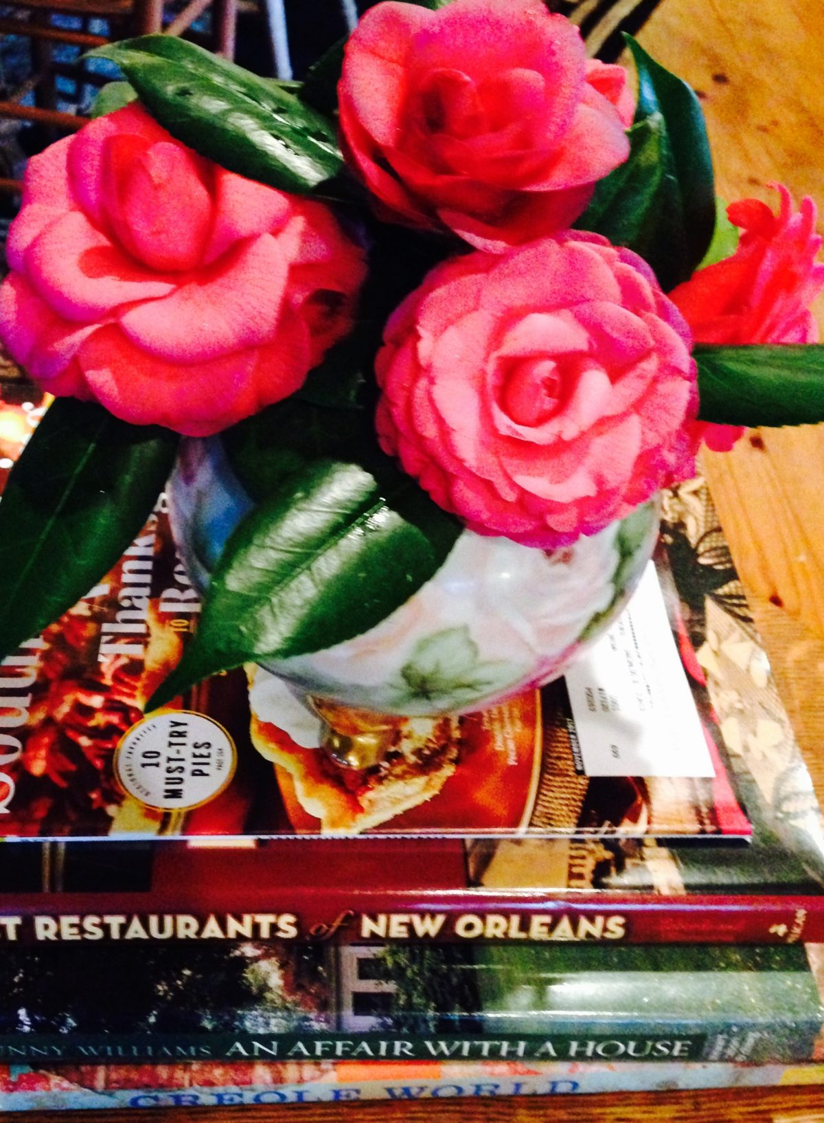 Pink camellia's in hand painted vase sitting on top Books about New Orleans
