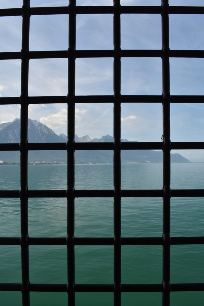 Castle window from Switzerland looking at Mountains and water www.diningwithmimi.com